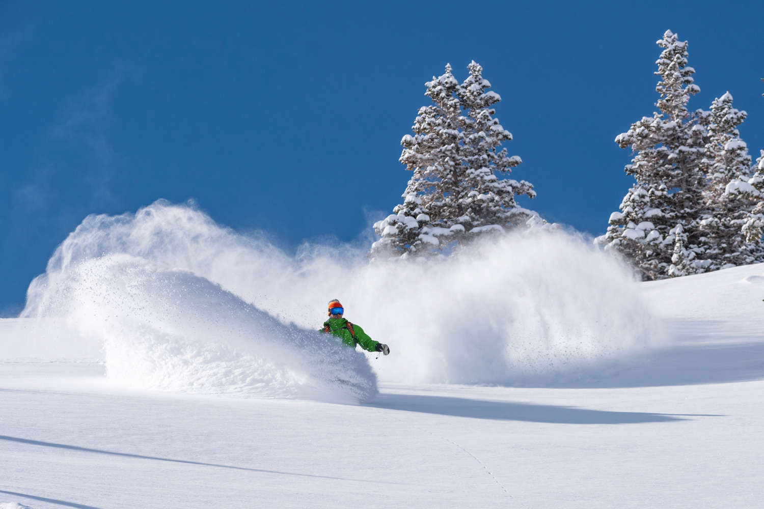 snowboarder making deep powder turns