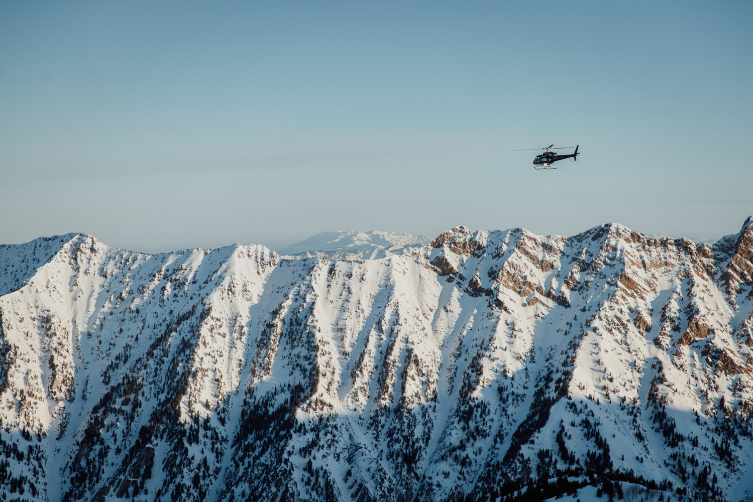 helicopter flying over tree and snow covered peaks