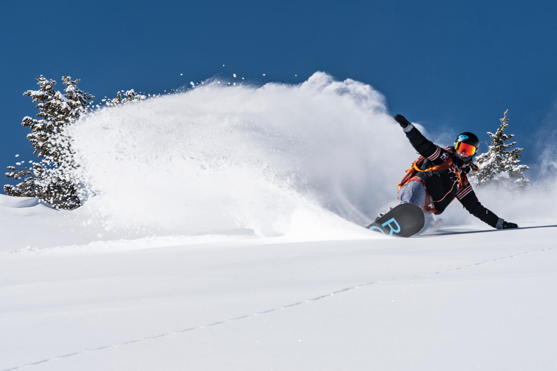 snowboarder making powder turn