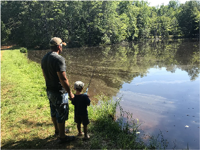 Parent and child standing by a lake