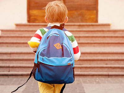 Little boy with backpack heading to school
