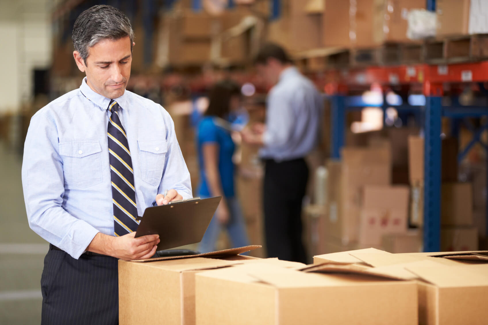 Business owner in warehouse with clipboard