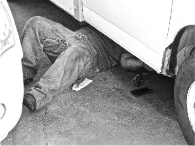 Mechanic under car fixing car