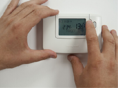 Person setting a thermostat