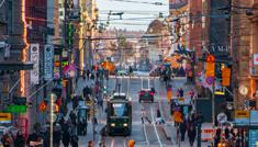 Vilkas katunäkymä Helsingin keskustasta, missä ihmisiä, auto, pysäkit, kiskot ja raitiovaunu.