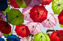 Useita erivärisiä sateenvarjoja ilmassa alhaalta päin kuvattuna.