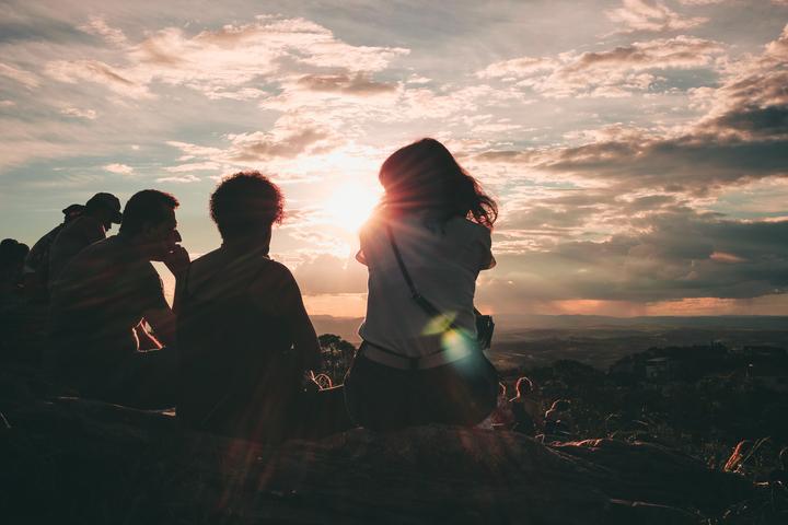 Ihmisiä istumassa vuoren rinteellä takaa päin kuvattuna. Katselevat auringon laskua.