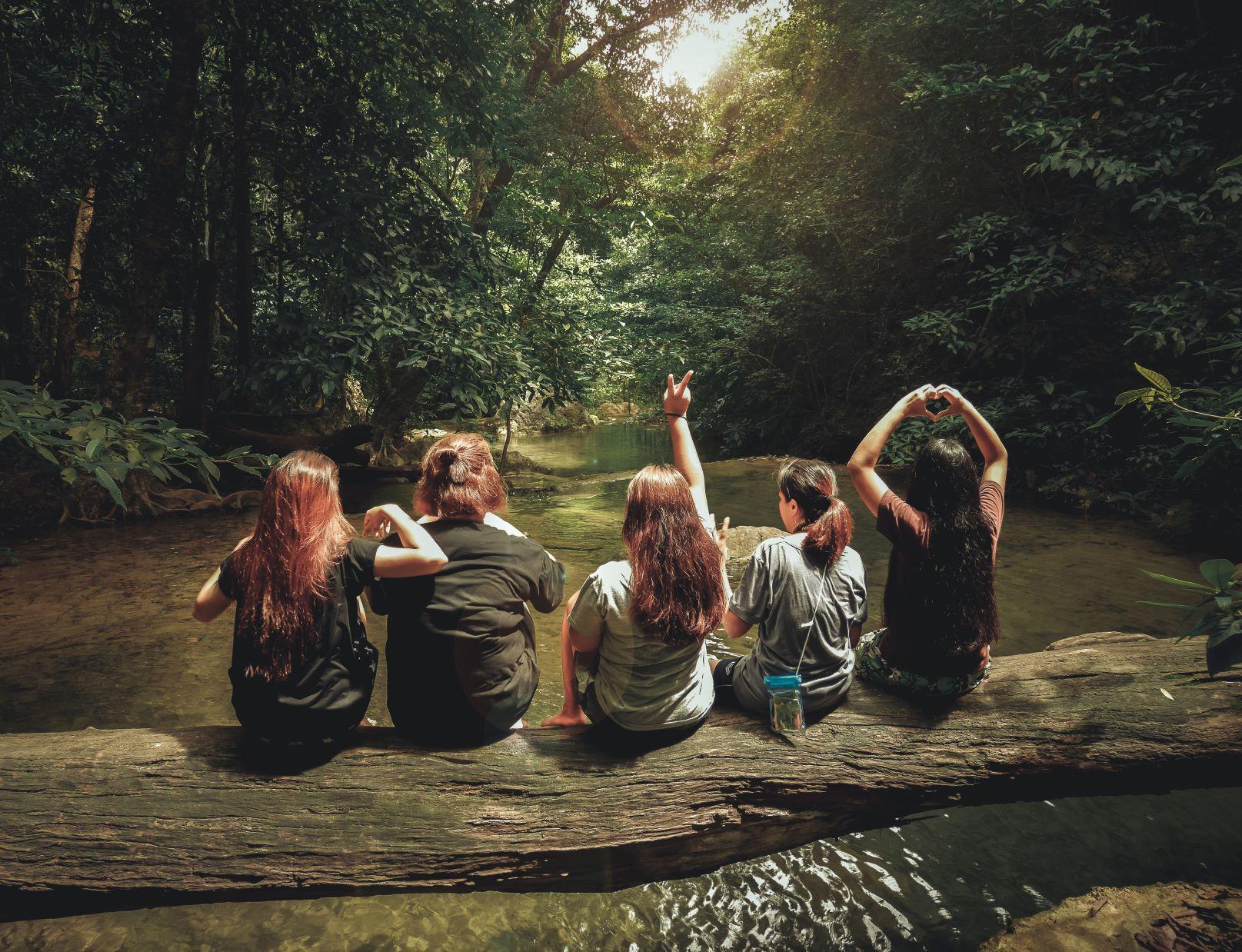 Viisi naista istuvat joen yläpuolelle kaatuneen puunrungon päällä. He ovat selästysten kuvaan nähden.