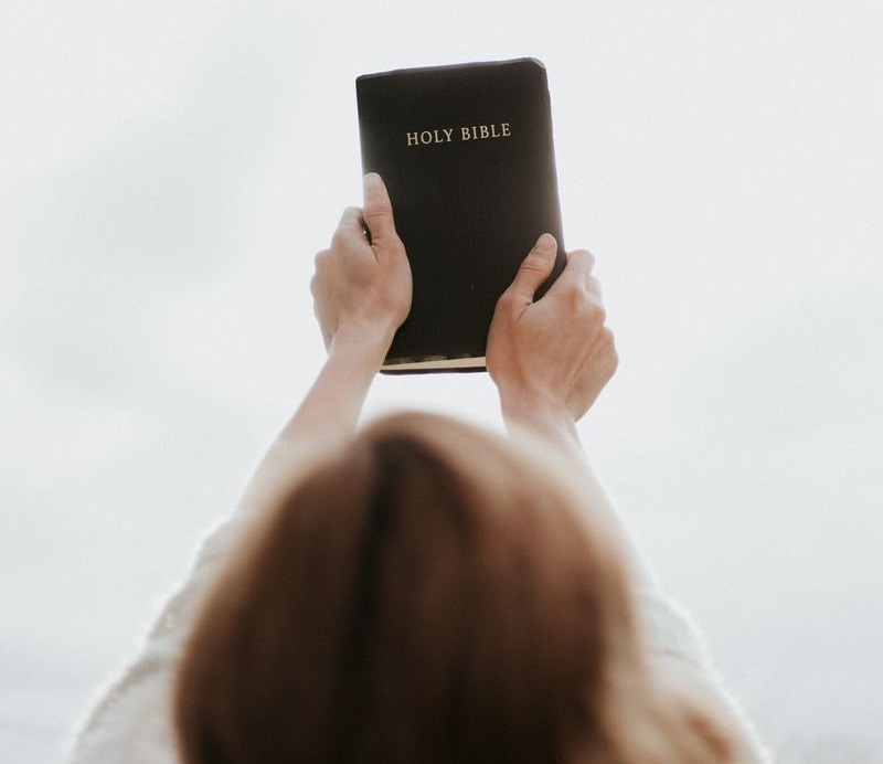 Woman Holding Up Bible