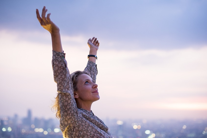Woman raising hands to sky.