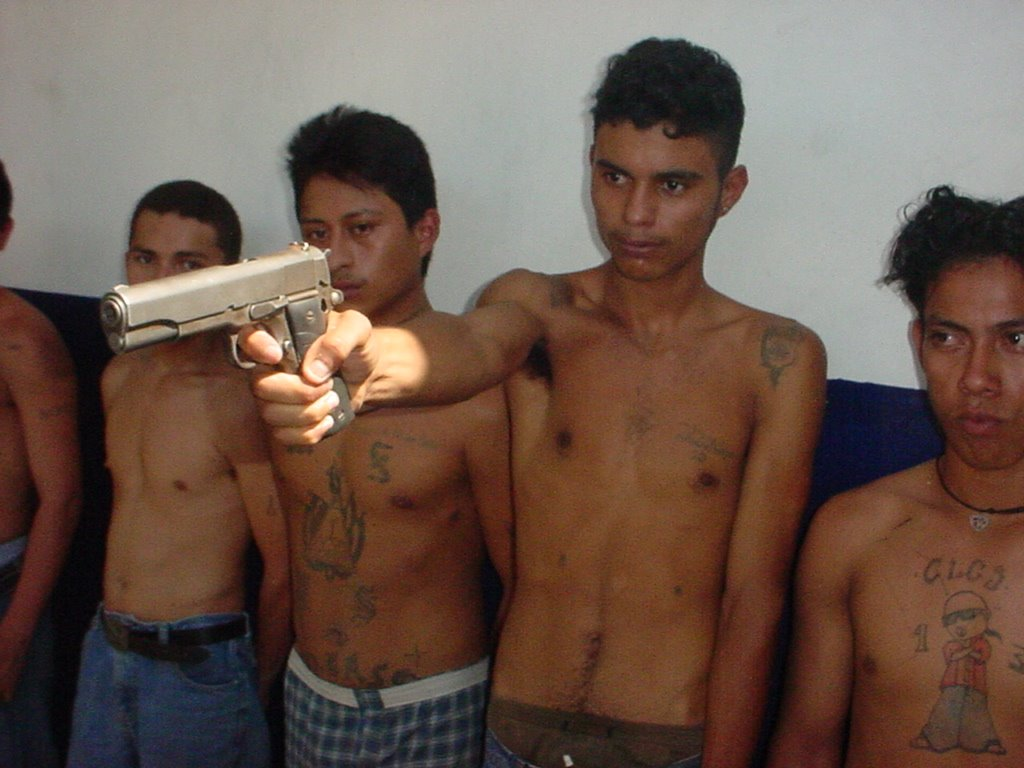 Young MS-13 gang member aims a gun