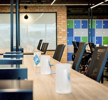 Imagem: Várias Canecas da ZUP sobre a mesa de escritório com cadeiras ao redor.