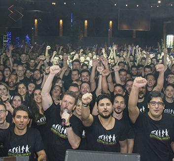 Imagem: Equipe da Zup com os braços levantados na festa de confraternização