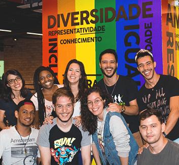 Imagem: Grupo de pessoas atrás da bandeira LGBT