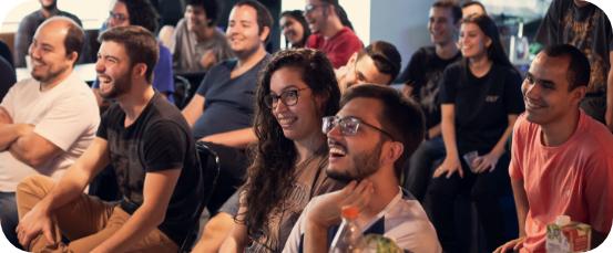 Foto de uma turma de Zuppers sentados em um auditório assistindo uma palestra. Boa parte deles sorri ou gargalha.