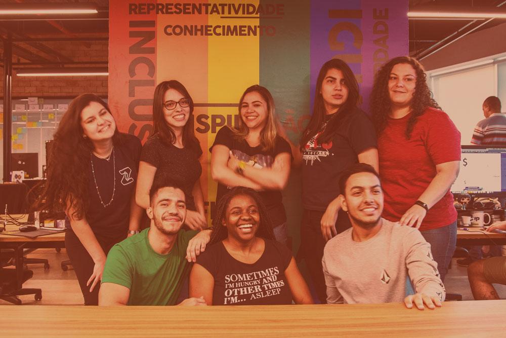 O grupo de zuppers sorridentes das guildas de diversidade posam em frente a um pilar do escritório de uberlândia decorado com as cores do arco-íris e palavras inclusivas.