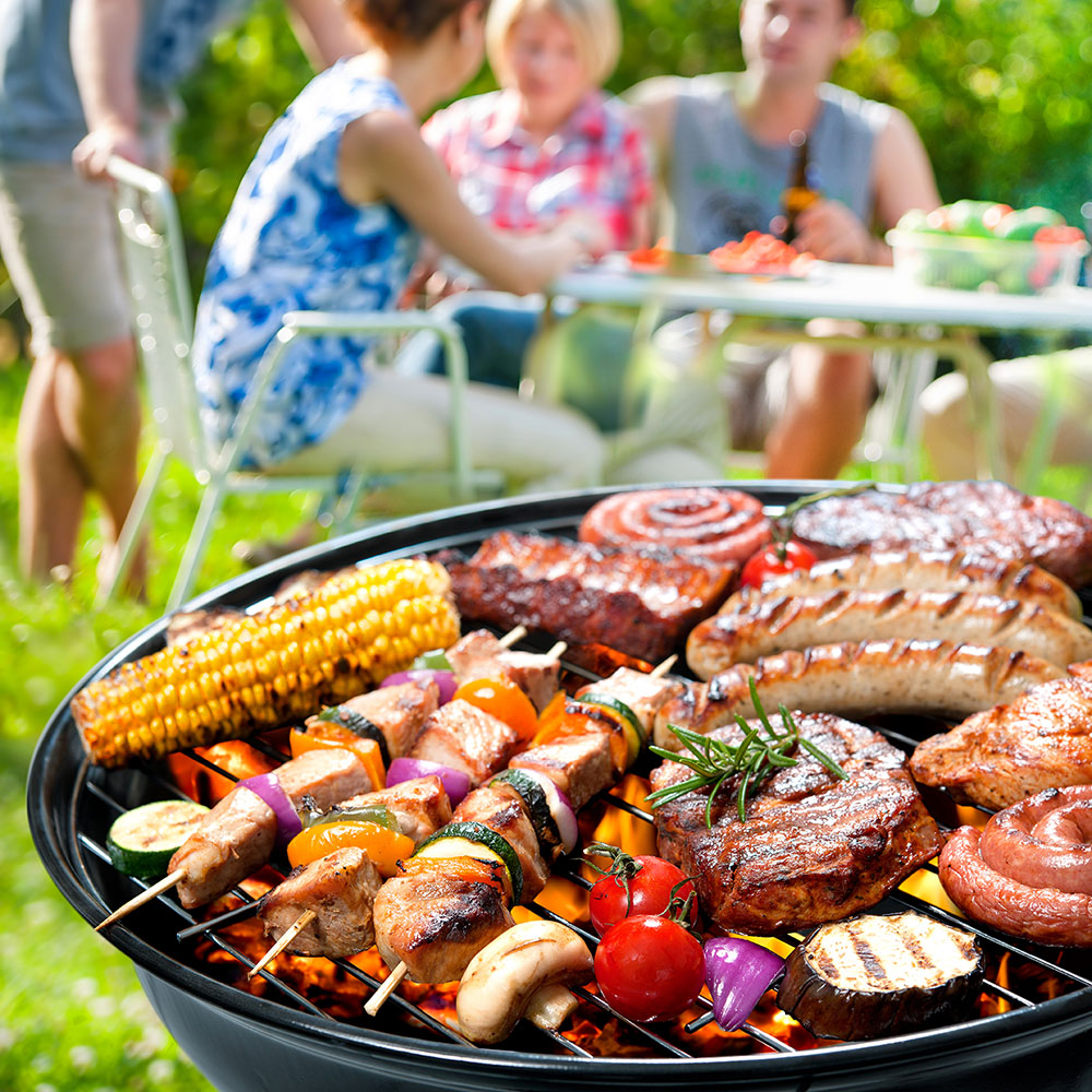 Assortment of meats and vegetables on the grill at a cookout.