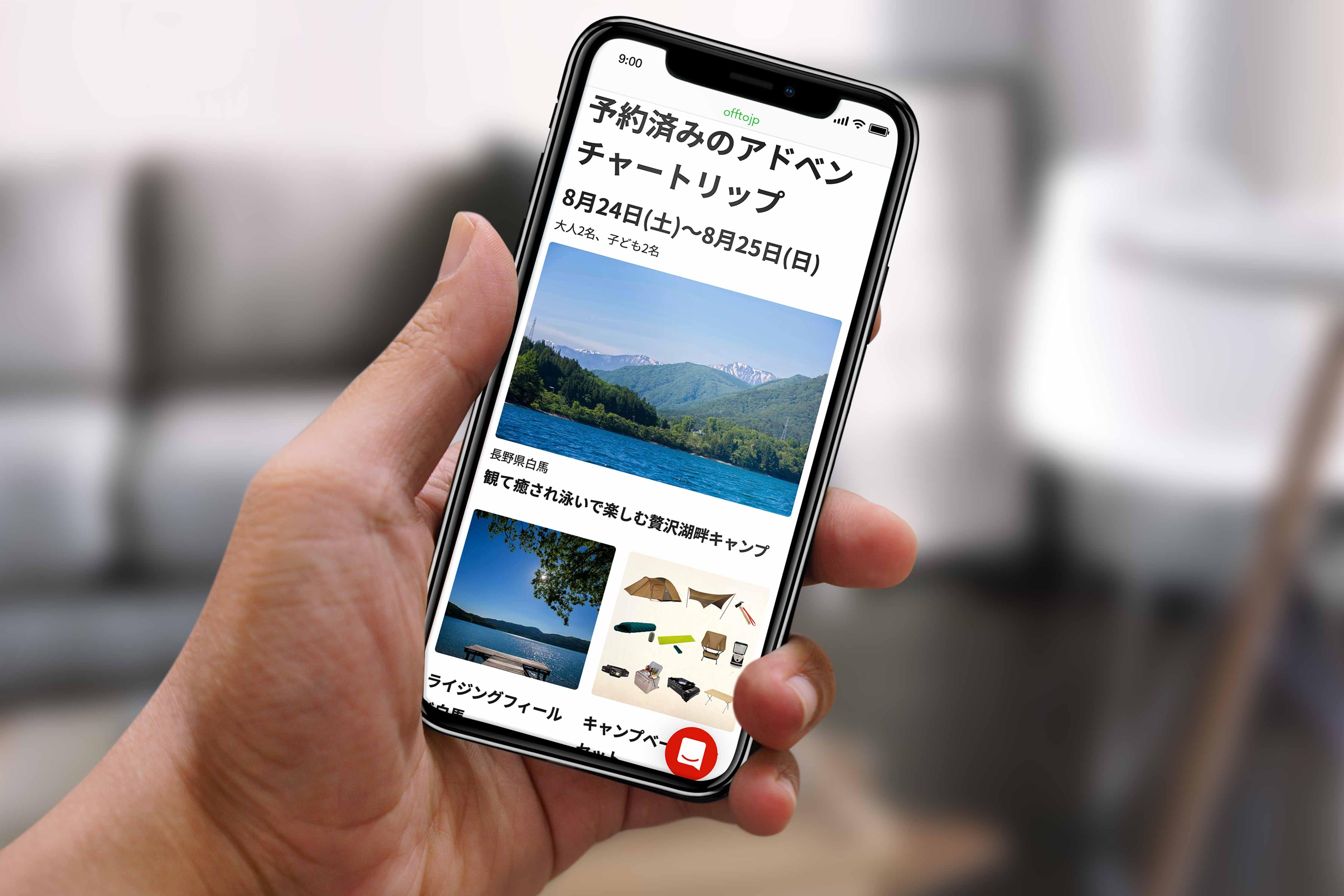 予約情報の画面がうつったiphoneXを持つ手