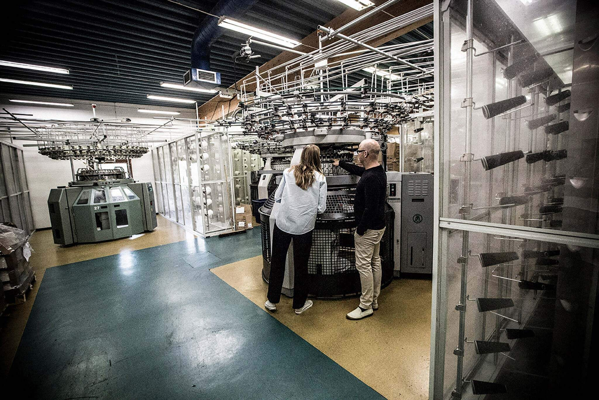 Lisa Bergstrand inspects a knitting machine with a man at Märback Tricot, in southern Sweden