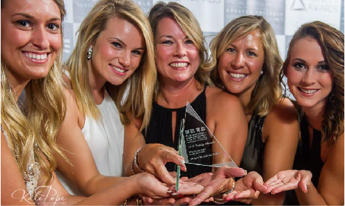 Group of happy women holding trophy created by FiveStar Awards & Engraving in Cary NC