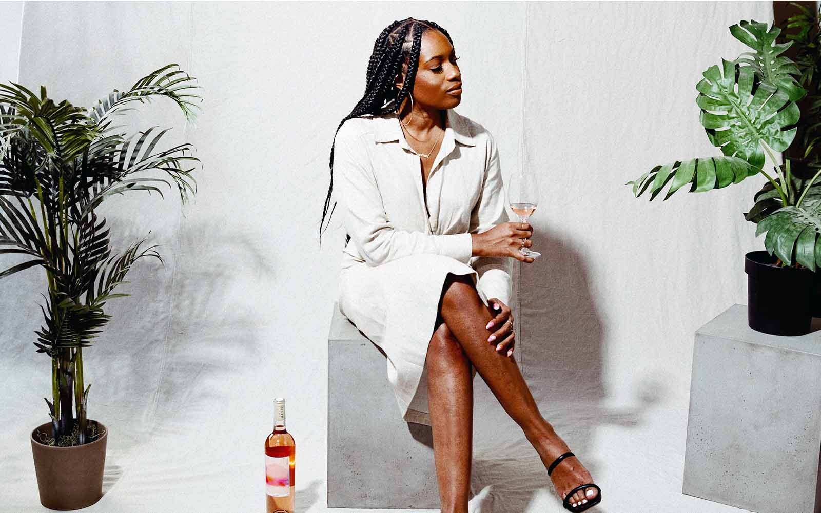 Woman drinking wine while sitting on concrete block in studio setting