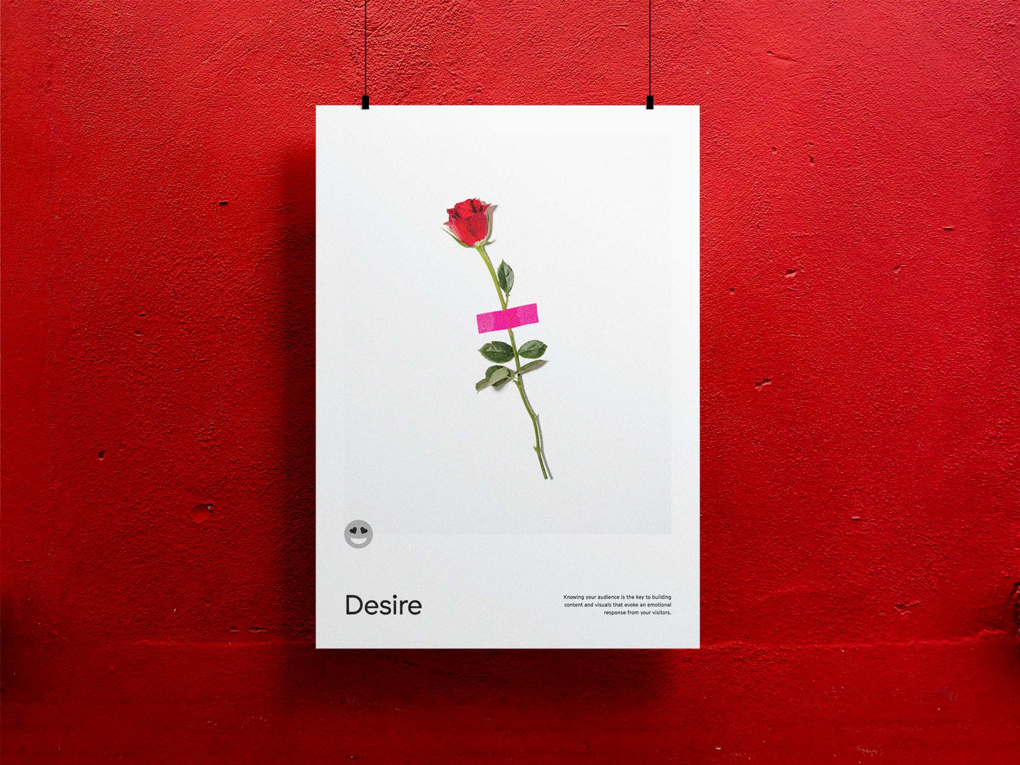 Desire poster with image of a red rose taped to a white wall with hot pink tape
