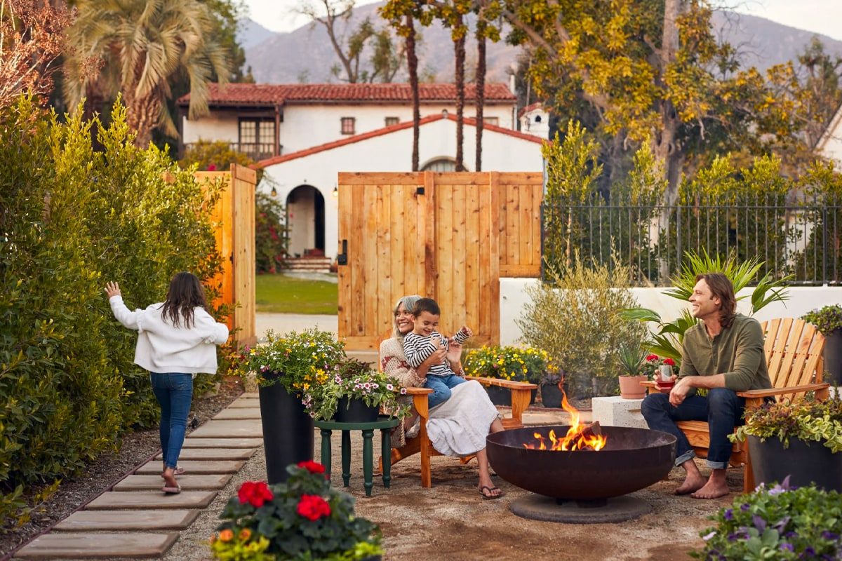 Bloomscape lifestyle photo that shows a family sitting in a yard on wood adirondack chairs around an iron fire pit