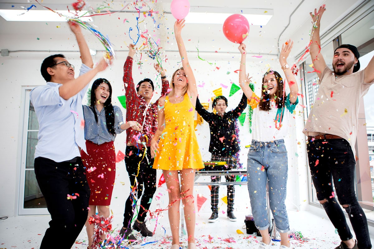 Seven people jumping and celebrating a work anniversary with streamers and balloons.