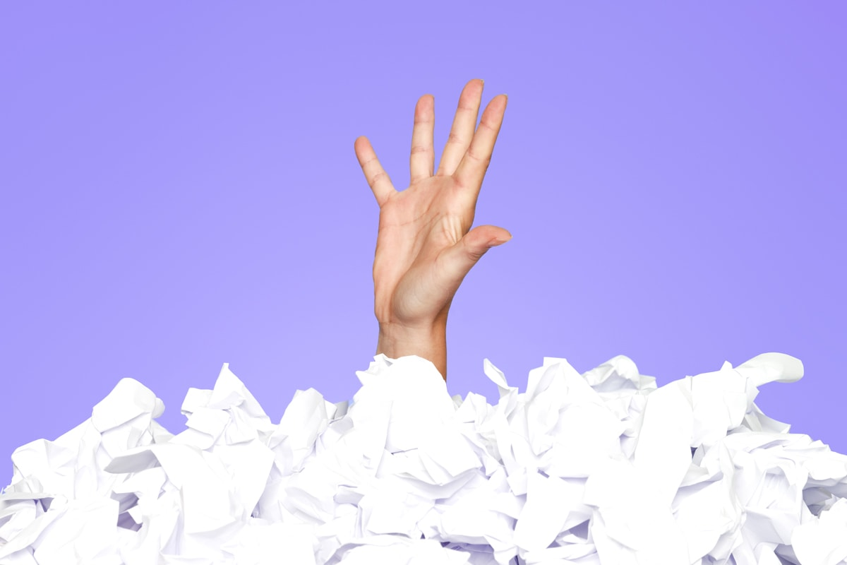 A pile of crinkled paper with a hand sticking out.