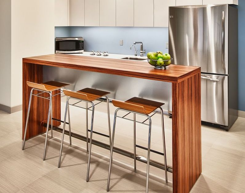 Kitchen with three wooden bar stools at a wooden table with apples on it and a fridge in the background.