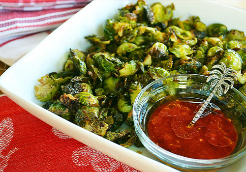 Brussels sprouts veggie chips in a plate with chilli dipping sauce on the side