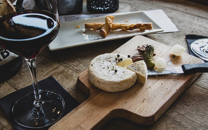 A photo of a wine glass alongside a cheeseboard great idea for a virtual team building cheese and wine