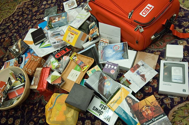 A photo of an event gift bag by TED containing snacks, sponsor goodies, and stationery