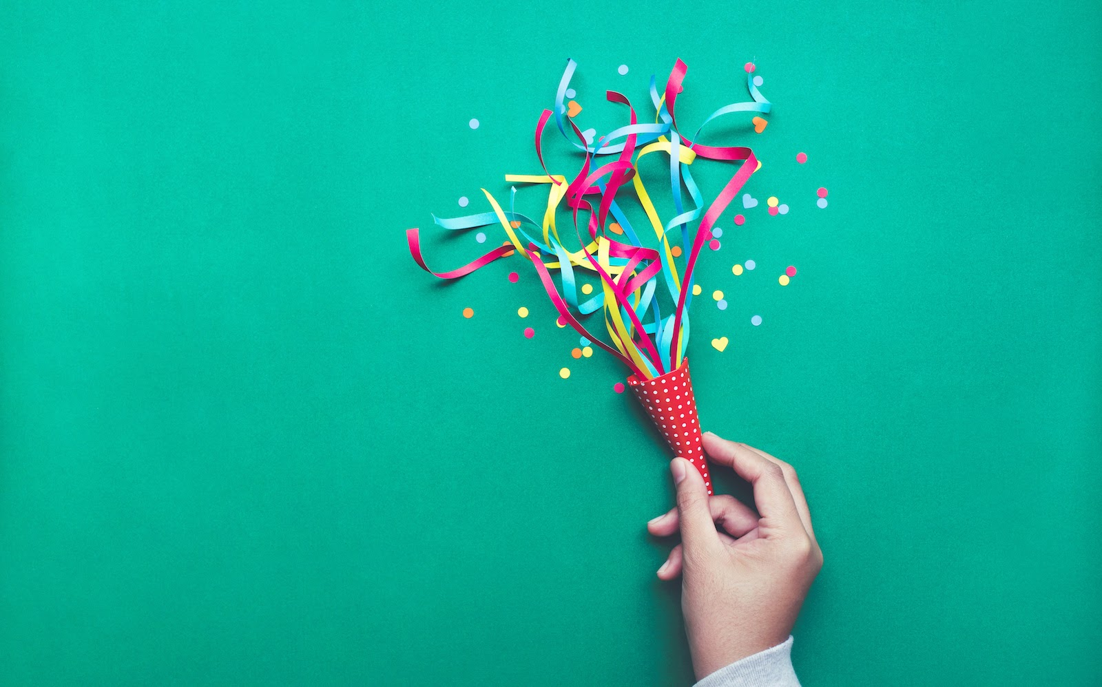 A hand with streamers and confetti to celebrate the benefits of event marketing