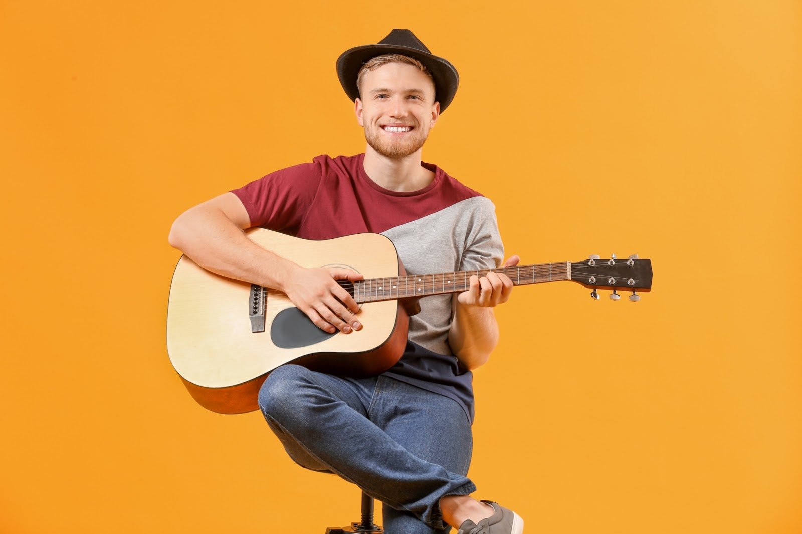 A man plays guitar as part of a virtual happy hour activity
