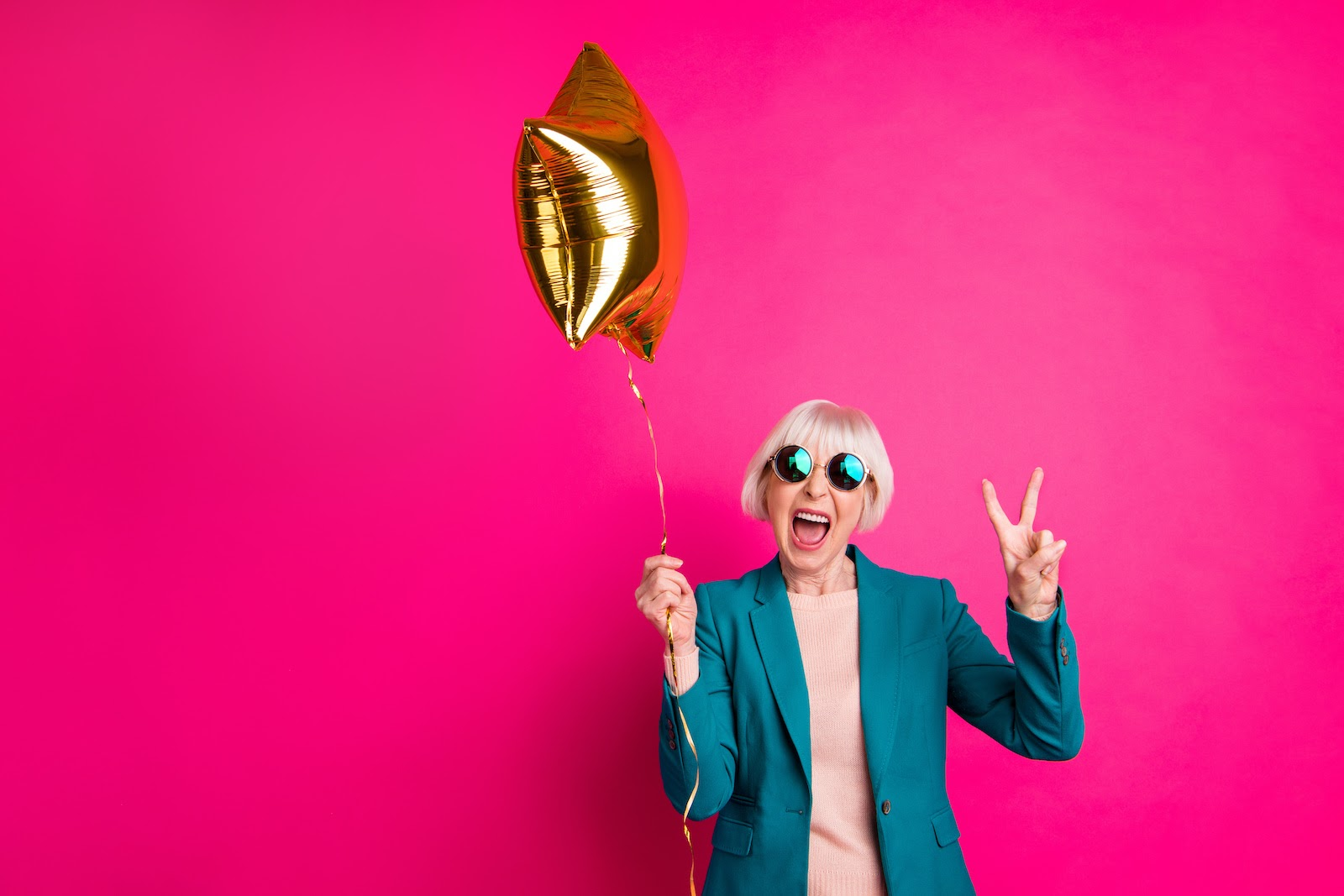 An older woman holds a party balloon in front of a hot pink background