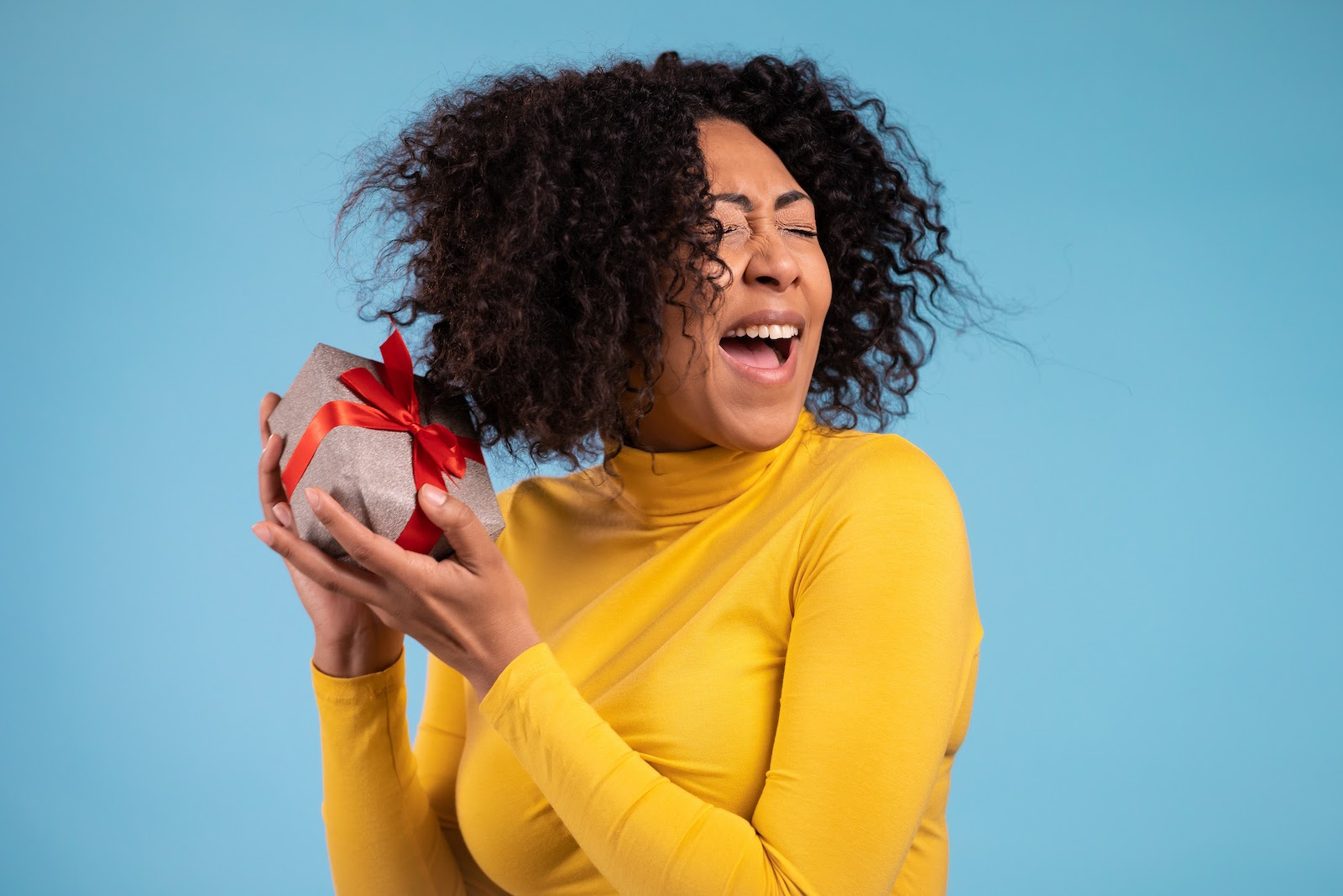 A happy, excited woman holds a present from a corporate gifting program