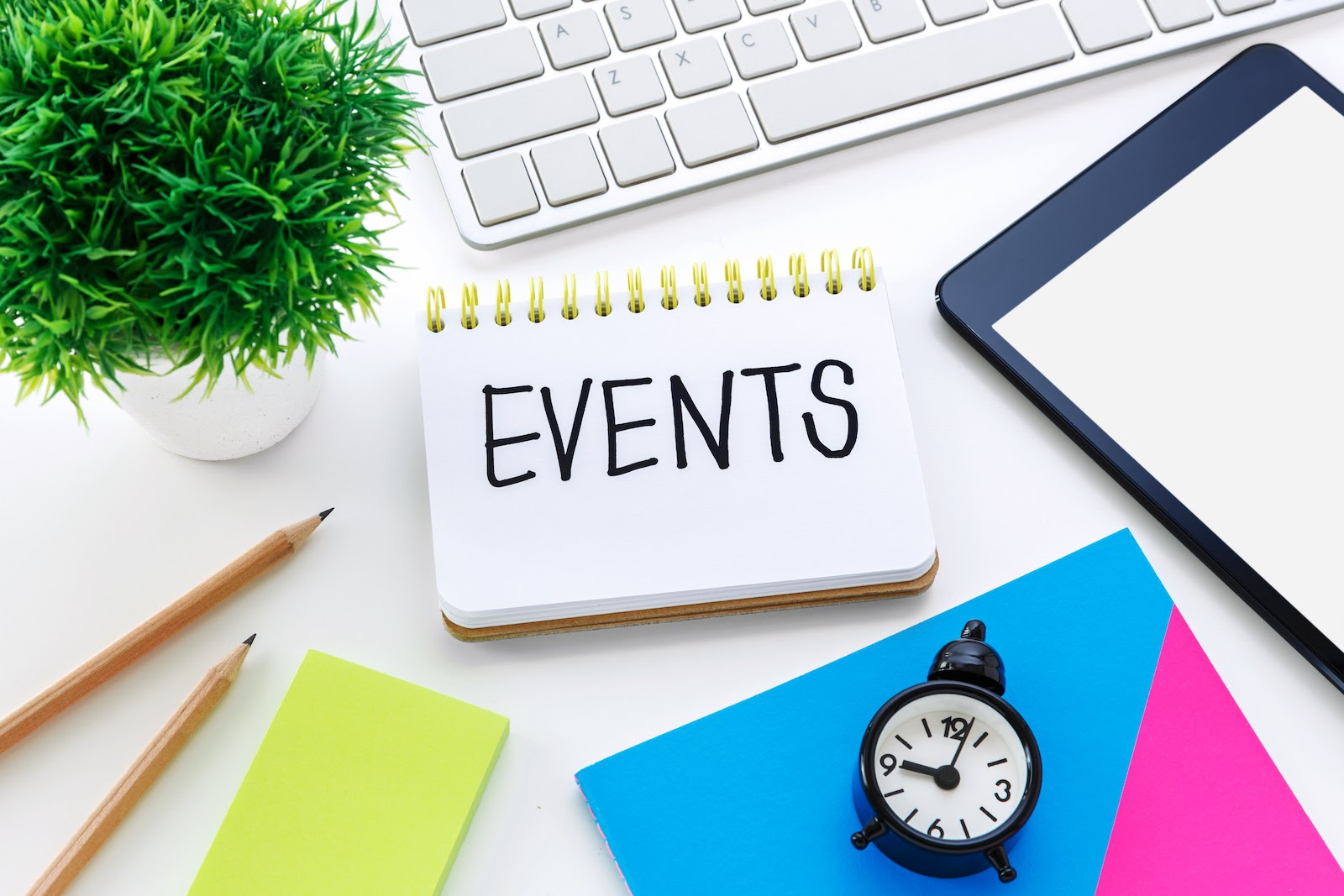 Note book, pencils, keyboard, clock, and other item you need to make an event planning checklist