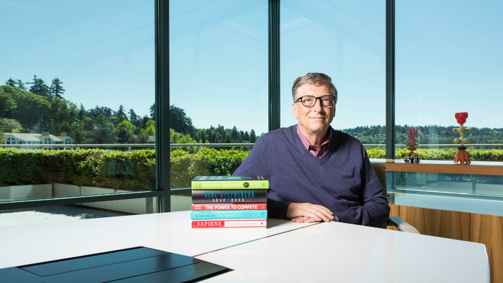 Bill Gates next to a stack of books