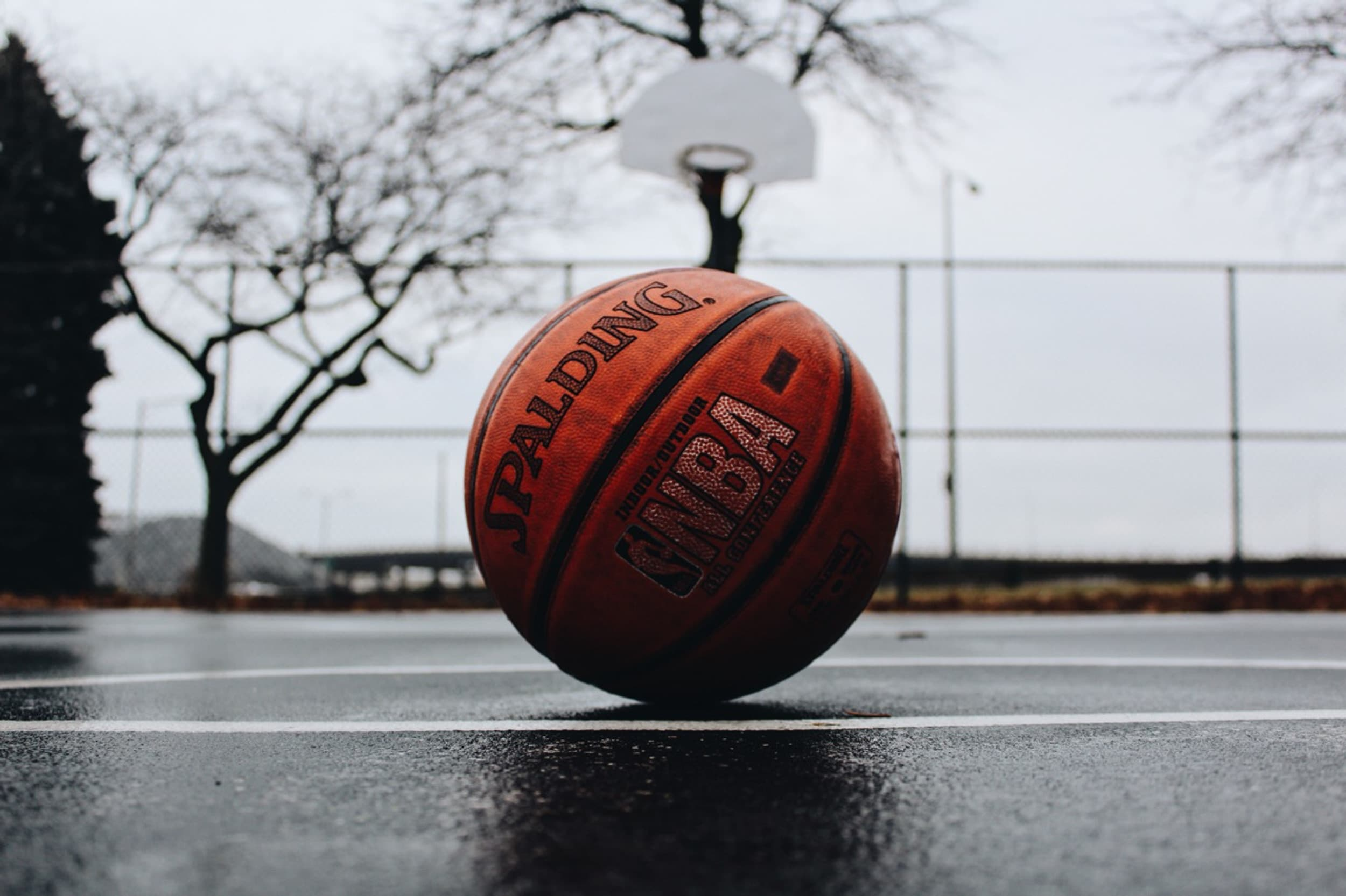 Spalding NBA basketball on a blacktop court on a rainy day
