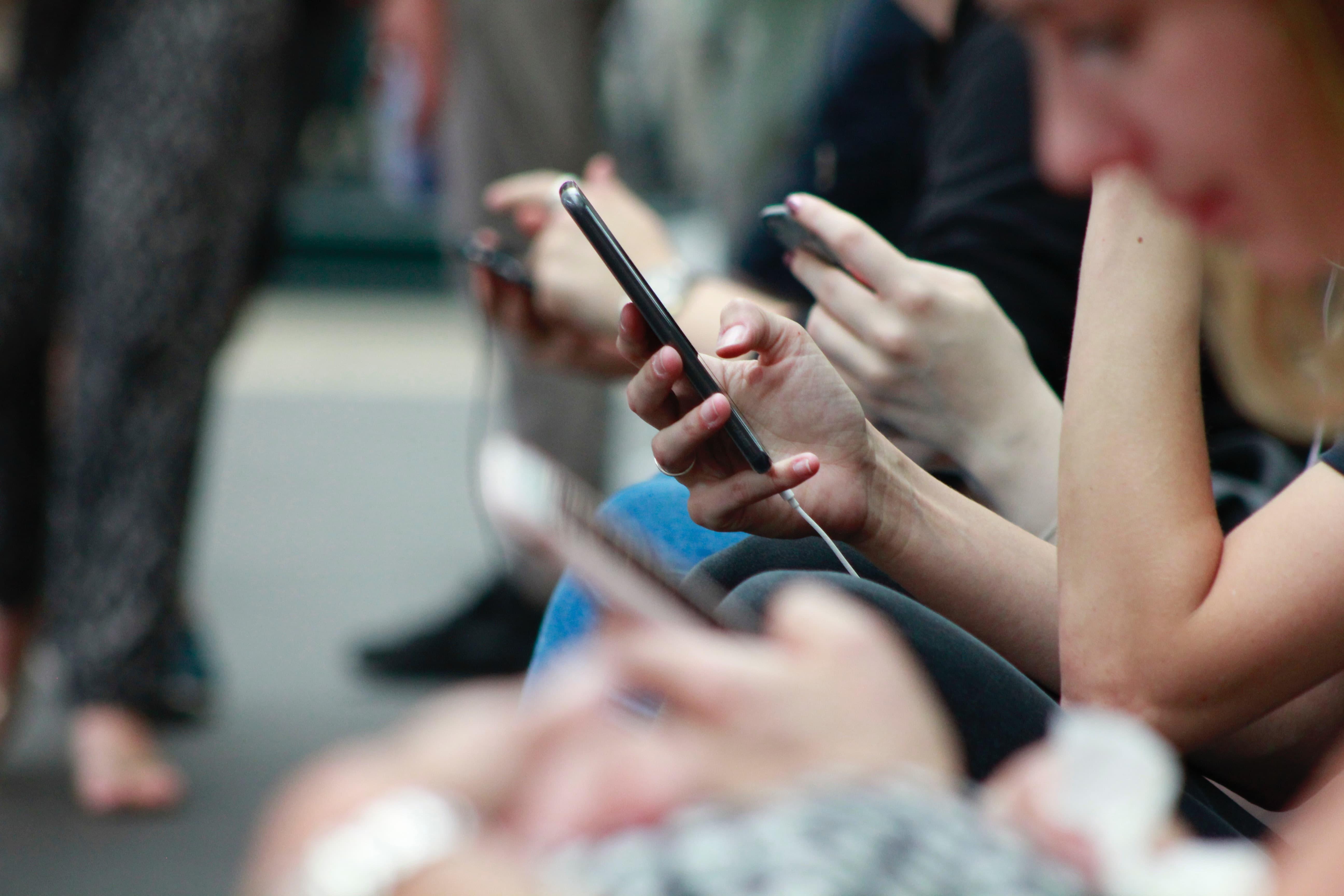 people sitting down on their phones