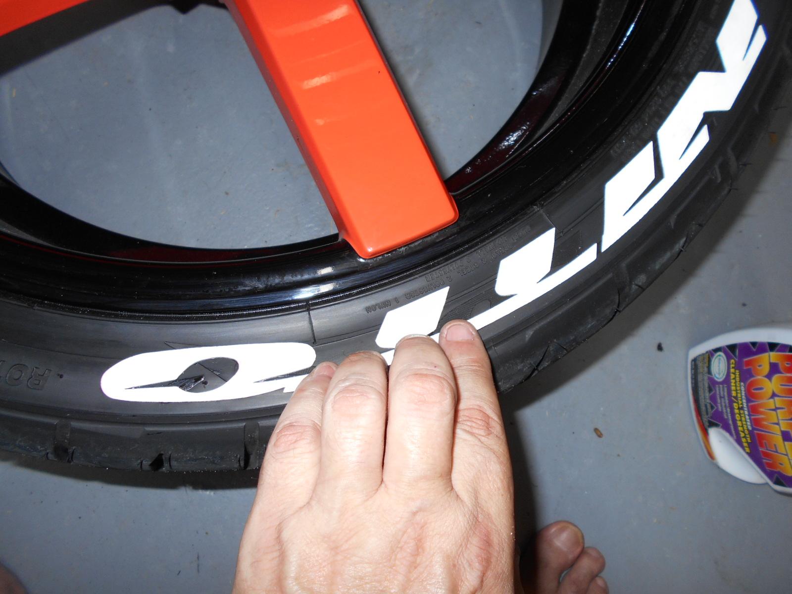 Pressing down treadwear graphics on tire