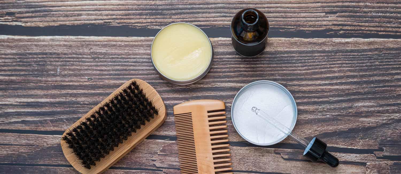 Flat Lay with beard oil, beard balm, beard comb and brush.