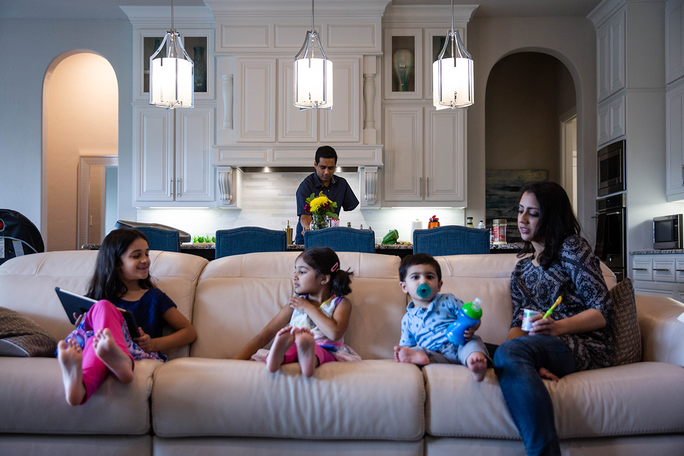 Khan cooks lunch for his wife, Ayesha, and children, Nazneen, 7, Yasmeen, 4, and Rehan, 1, in their home in Southlake, Texas.