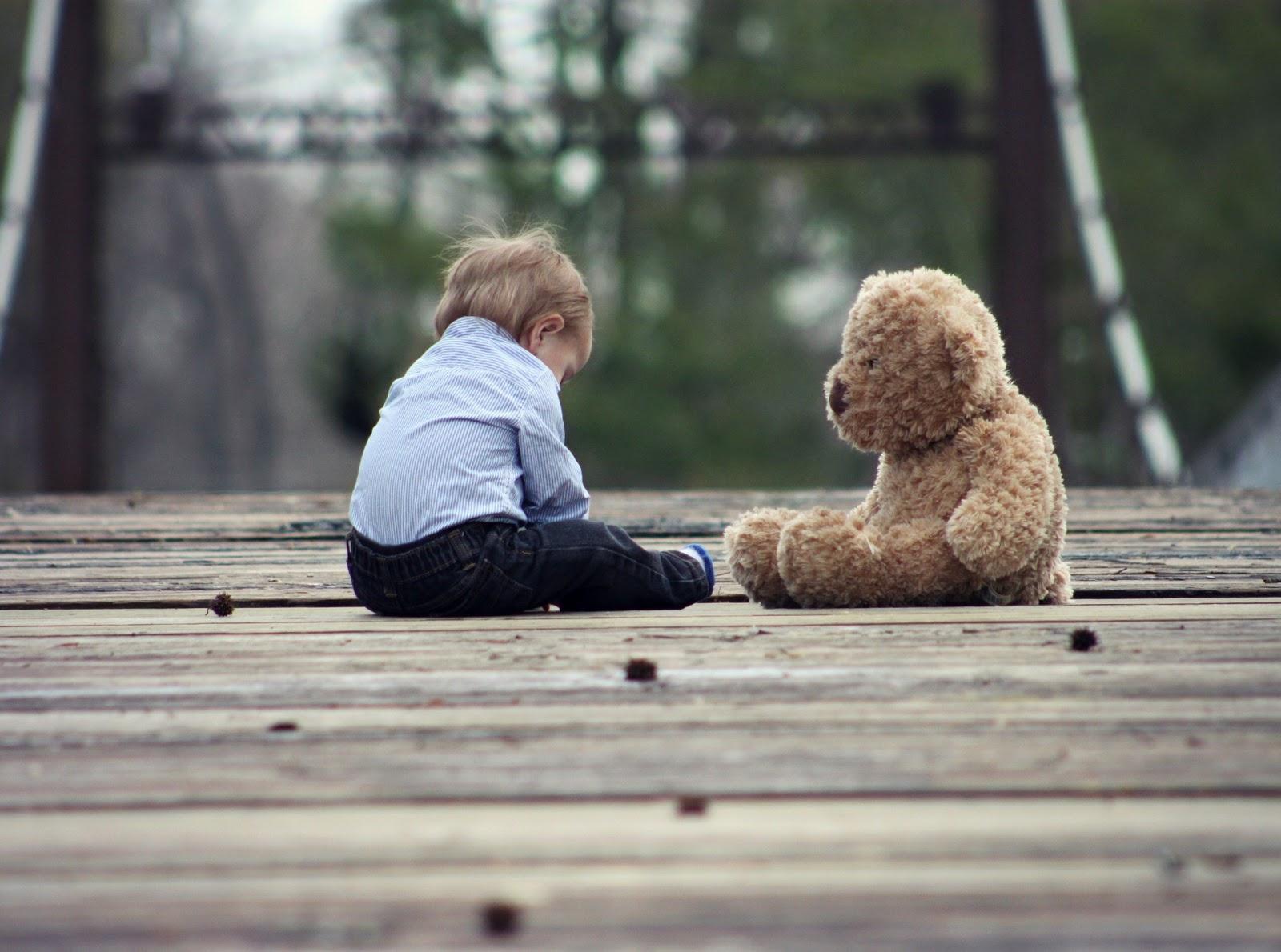 sad child sitting next to teddy bear