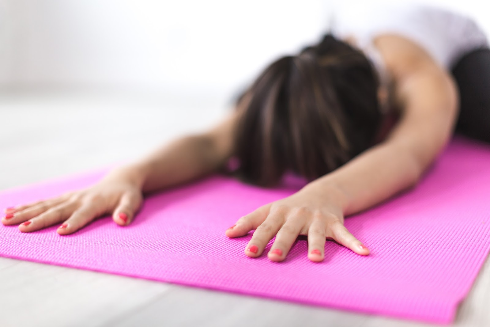 brunette woman practicing yoga on pink mat
