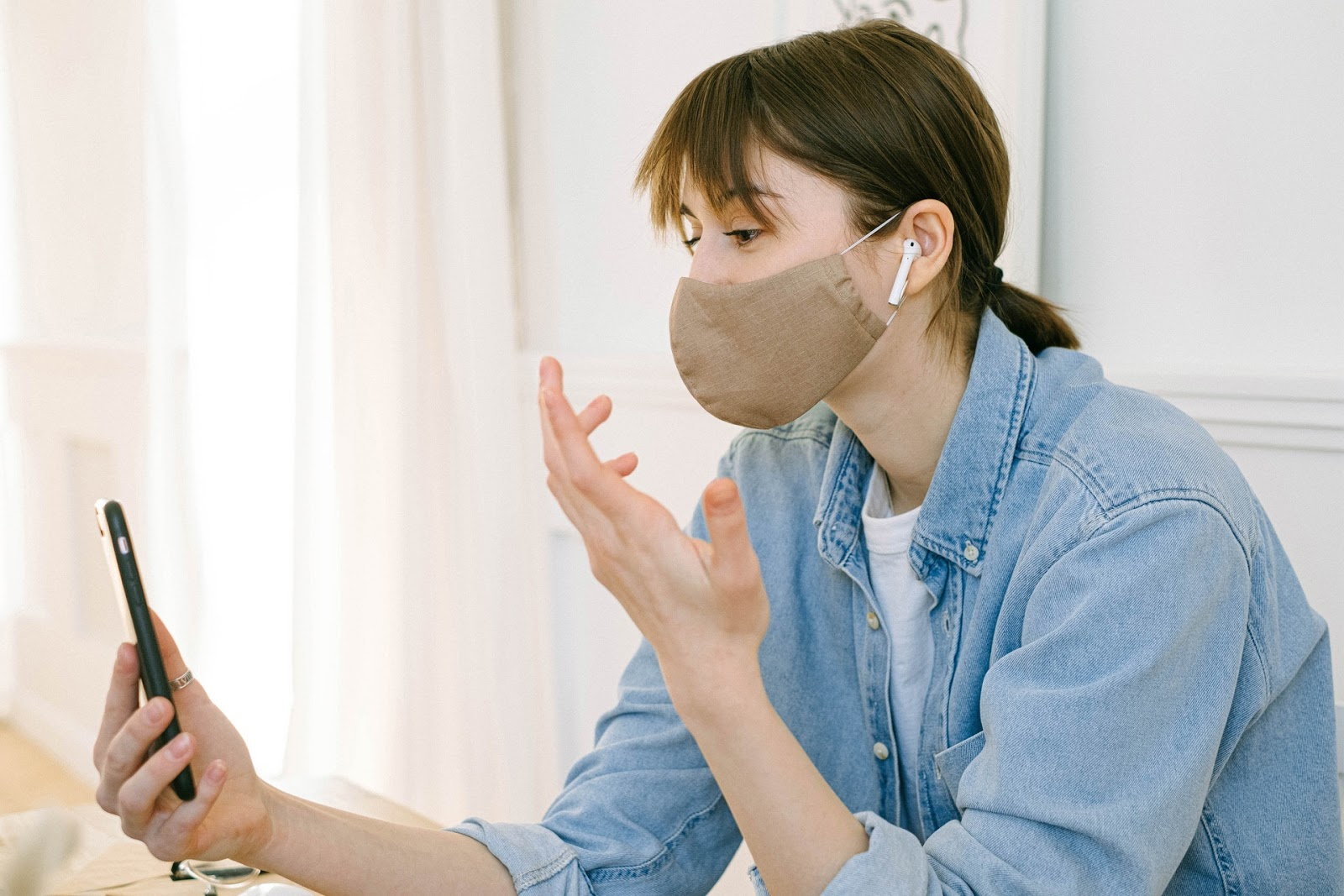 woman in tan mask video chatting with friend