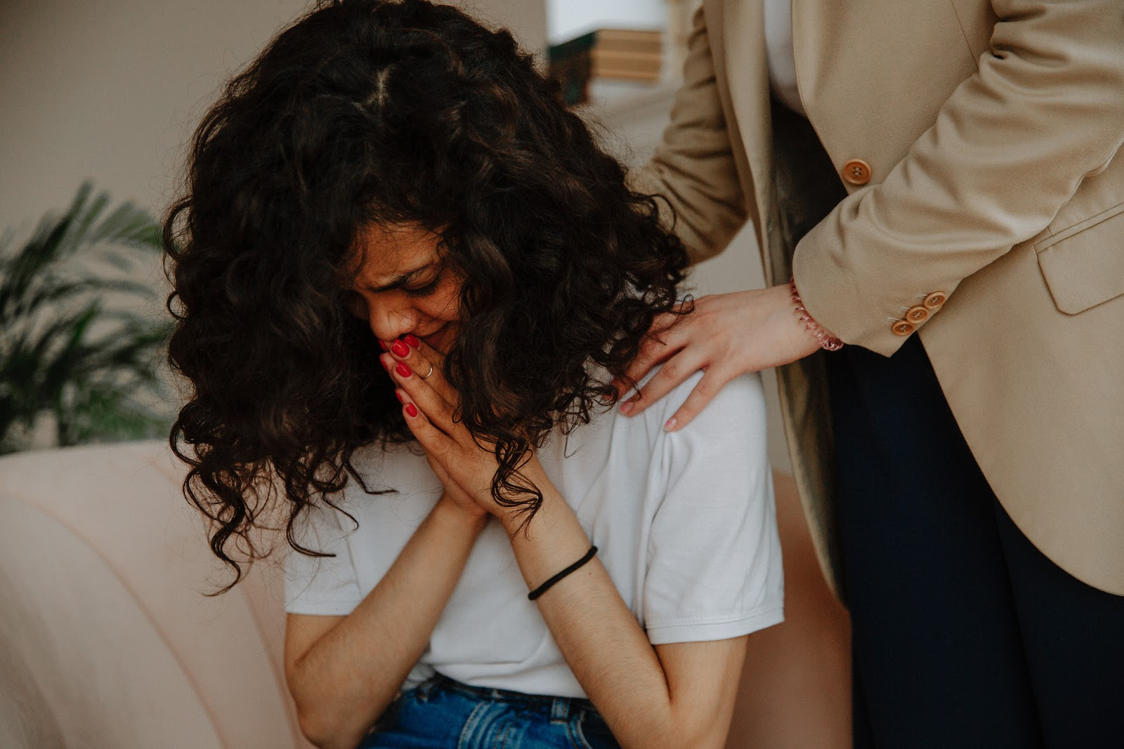 person comforting upset young woman