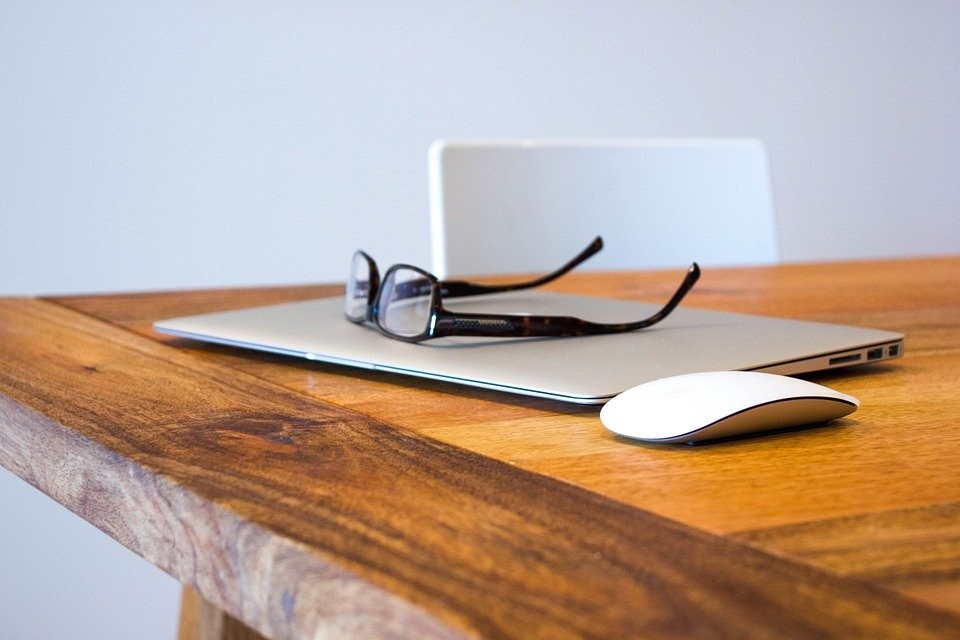 pair of glasses on macbook laptop