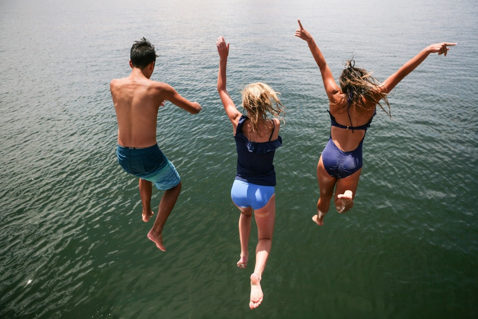 group of people jumping into water